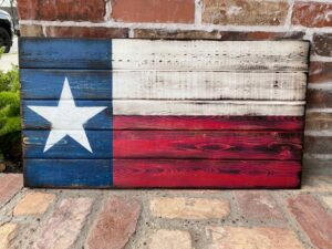 Large wood pallet painted to look like a rustic Texas flag, with blowtorched edges. Laying against a brick wall and floor.