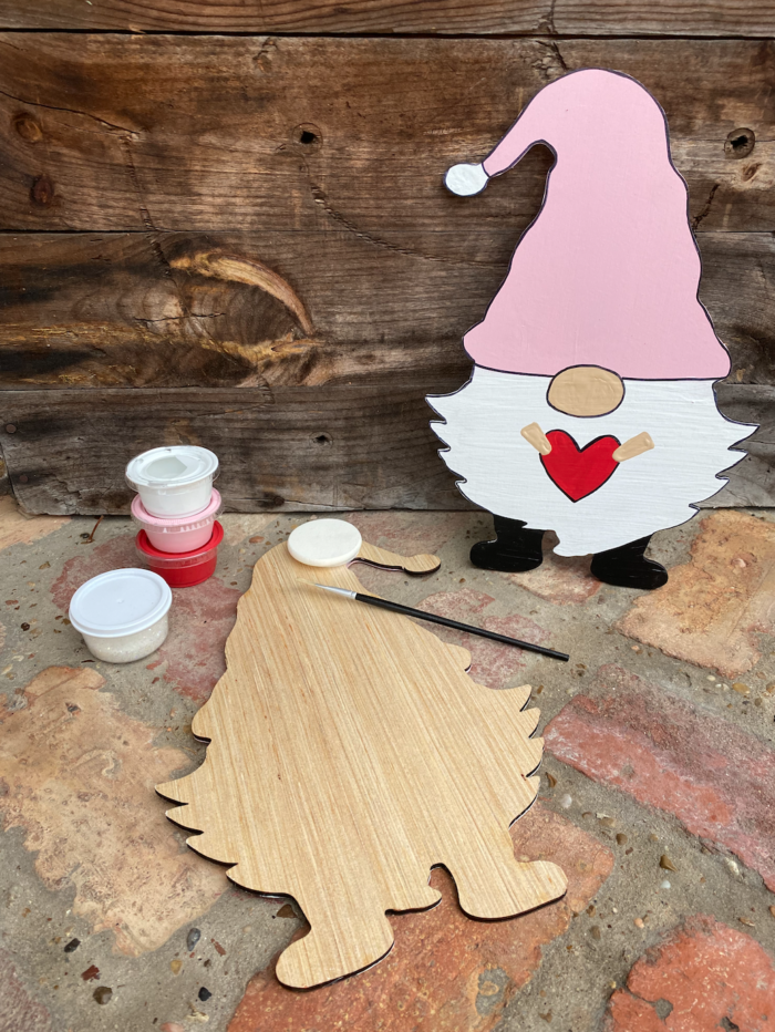 Blank wooden gnome cut out laying on brick background surrounded by paint cups, paintbrushes, and sponges, displaying what is included in the kit. A fully painted gnome cutout sits nearby with a white beard, a pink hat, and holding a red heart.
