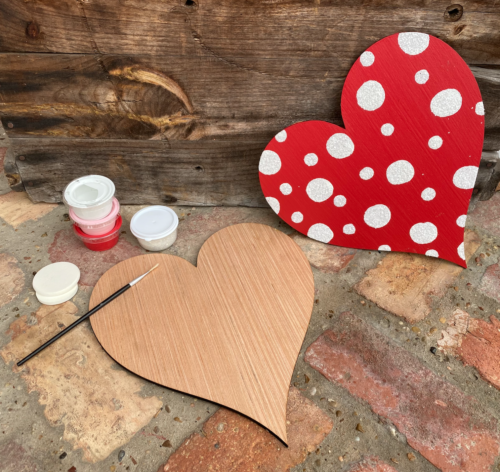 Blank wooden heart laying on brick background surrounded by paint cups, paintbrushes, and sponges. A red and white polka dot heart sits nearby.