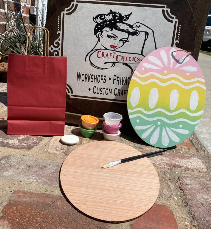 Blank wooden egg cut out laying on brick background surrounded by paint cups, paintbrushes, and sponges, displaying what is included in the kit. A fully painted egg cutout sits nearby with a rainbow pastel background and white detailing.